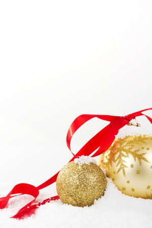 christmas decorations with white background: Gold Christmas decorations in white snow for a background
