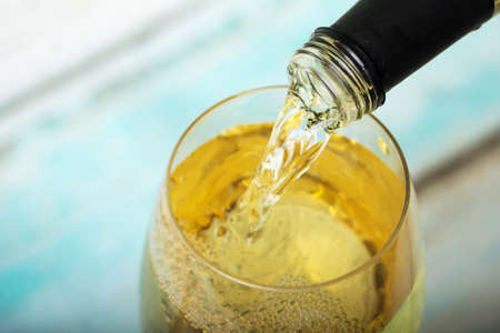 Glass of white wine being poured from a bottle