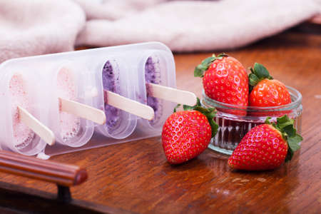 Homemade strawberry ice lolly on a rustic background Stock Photo