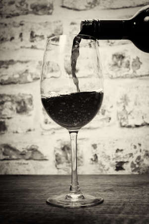 full bodied: Glass of full bodied red wine being poured from bottle