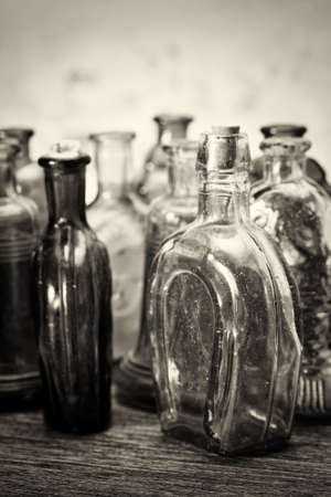 Selection of coloured glass bottles on a rustic background