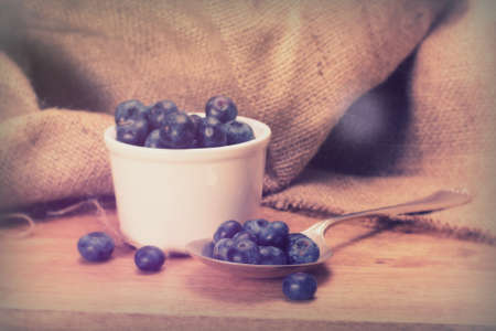 Pot of blueberries with spoon on a rustic wooden background
