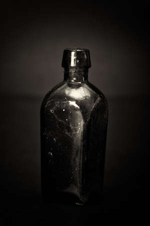 Old colourful vintage bottles against a dark background Stock Photo