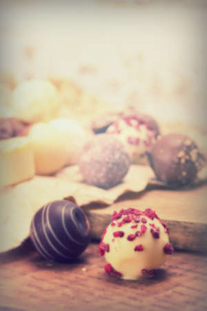 Selection of delicious chocolates on rustic background