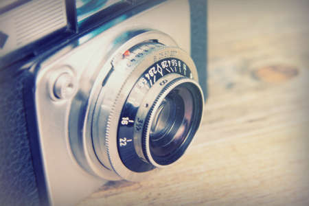 Old vintage retro camera on a wooden background