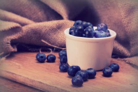 Pot of blueberries on a rustic wooden background Standard-Bild