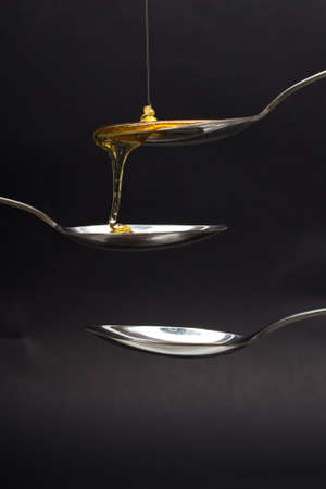 Honey pouring from a spoon against a dark background