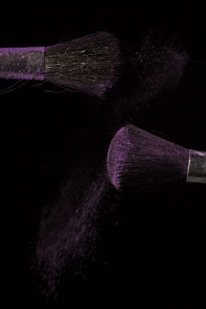 Make up brush with purple dust on a black background