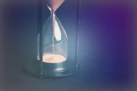 Large hourglass with pink sand against a black background Standard-Bild