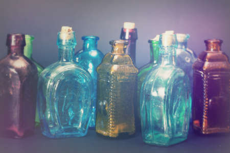 Old colourful vintage bottles against a dark background Standard-Bild