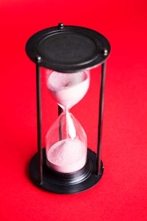 Large black hourglass against a bright red background