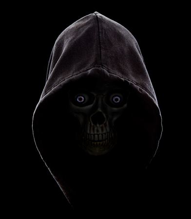 Black hooded scull in the dark with blue eyes.Fear in the dark.