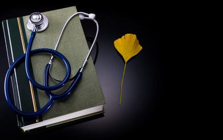 Stethoscope and medical book with Ginkgo leaf. Merge of traditional and herbal medicine.