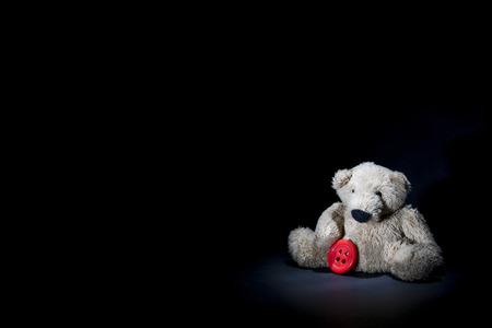 Little beige teddy bear holding red button.