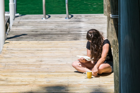 Young girl reading a book on a dock by the lake Stock Photo