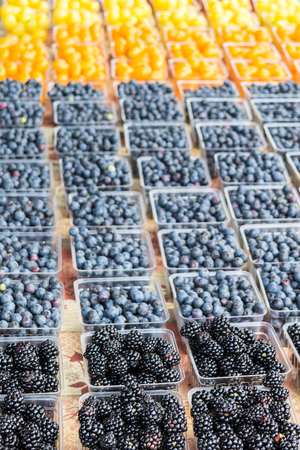 Blackberries, blueberries, and yellow cherry tomatoes at the farmers market during summer