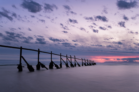The old fence at Strand running into the ocean at sunset - South Africa Stock Photo