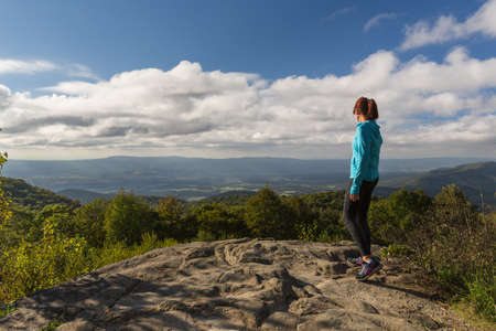 Woman inspirationally looking down from the Skyline Drive in the Shenandoah National Park, woman has this inspirational view across the valleys and mountains below Stock Photo