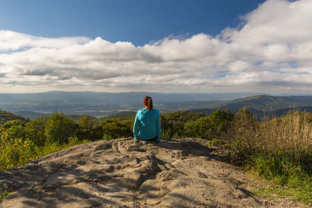 run down: Woman inspirationally looking out from the Shenandoah National Park
