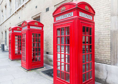 Threee Red London Telephone boxes all in a row in the City
