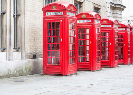 Five Red London Telephone boxes all in a row in the City Stock Photo