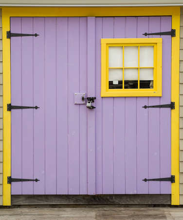 Purple And Yellow Barn Door With Padlock In Maine Stock Photo