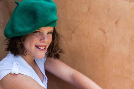 green beret: Young girl smiling wearing green beret Stock Photo
