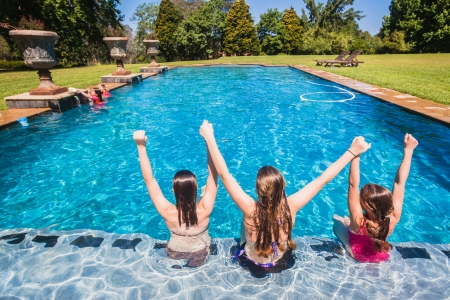 Young girls sitting in swimming pools waters unidentified on a summer blue day