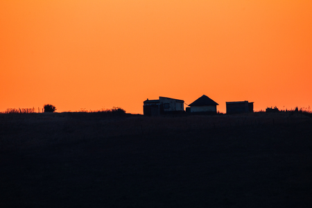 daw: African Dawn colors distant homes silhouetted on hills