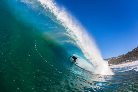swells: Water swimming angle of surfer inside large crashing hollow tube ride wave