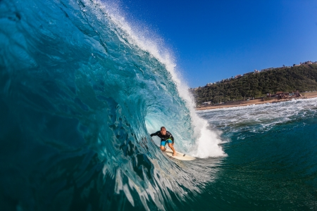 Surfer rides large hollow wave water swim view  Editorial