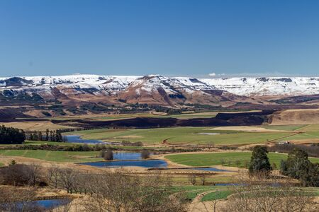 snow covered mountains: Snow covered mountains behind valleys and field with dams of water