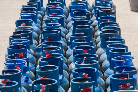 Gas bottles stacked in open yard at liquid petroleum LP filling station