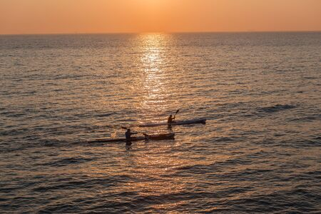 Surf-ski athletes paddling in reflecting ocean waters early morning sunrise photo