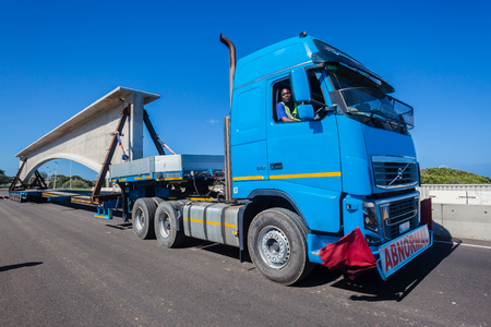 Heavy civil engineering contract with large concrete bridge section on abnormal truck trailer to installation site