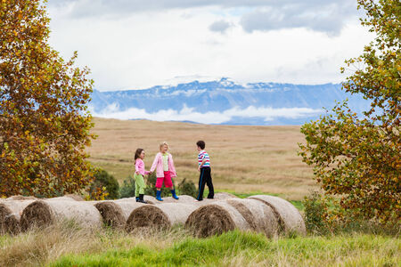 Young girls and boy standing talking on farm grass hay bales photo