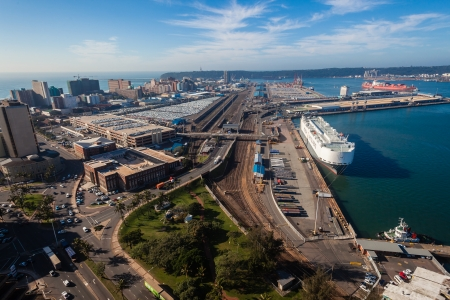 Durban harbor high elevation overlooking ship at car export terminal railway lines city building infrastructures and distant piers port shipping entry from the ocean