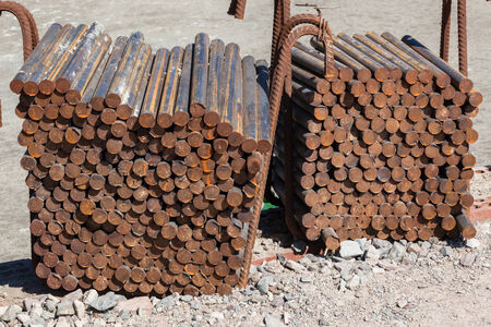 an insertion: Steel metal rod material  cut to size and stacked for concrete insertion in foundations at construction building site