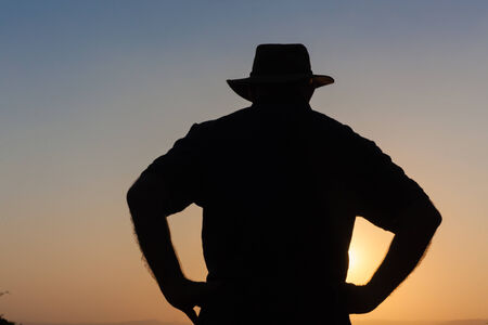 contrasts: Man unidentified wearing hat body outline contrasts silhouetted at sun setting late afternoon Stock Photo