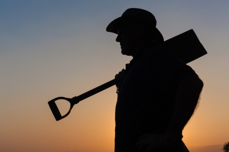 contrasts: Man unidentified hold work spade shovel with hat body outline contrasts silhouetted late afternoon sunset reflections Stock Photo