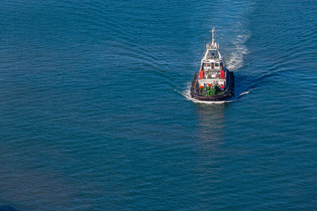 high powered: Harbor tug vessel high elevation air photo of the diesel powered vessel on the bay waters  Stock Photo