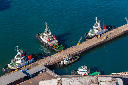 Harbor tug vessels moored alongside pier jetty High elevation air photo of the diesel powered vessels on the bay waters