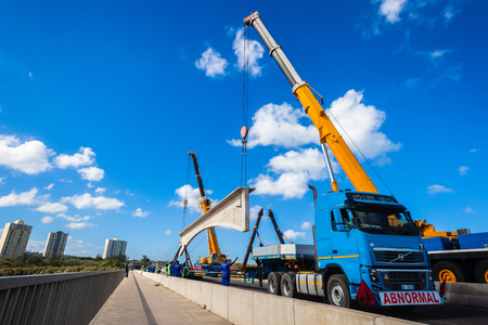 Construction heavy civil engineering rigging of large concrete bridge section lifted off truck and installed by two cranes