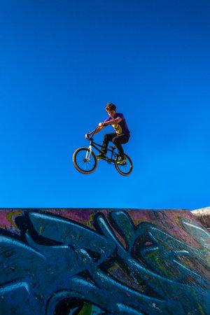 airs: Teen bmx biker air spins at park graffiti ramp in morning blue sky Editorial