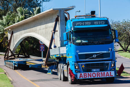 abnormal: Construction heavy civil engineering rigging of large concrete bridge section carried transported by truck and long trailer
