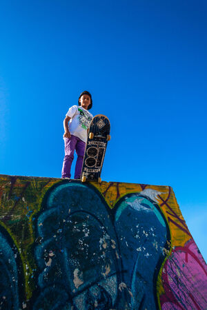 airs: Skateboarder ready to drop down park graffiti ramp in morning blue sky