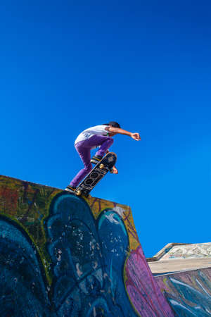 airs: Skateboarder dropping down park graffiti ramp in morning blue sky Editorial