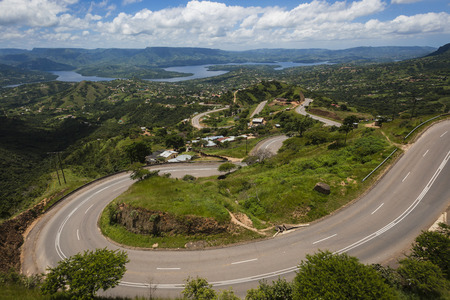 high winds: Inanda Dam entry high cliff valley road winds down and up the landscape Stock Photo