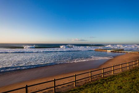swells: Morning blue sky overlooking ocean wave swells crashing breaking along shallow reef sandbars front of beach tidal pool Stock Photo