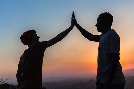 dignity: Friends caucasian african high five hands together against sun setting landscape